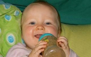 Bébé souriant avec un biberon